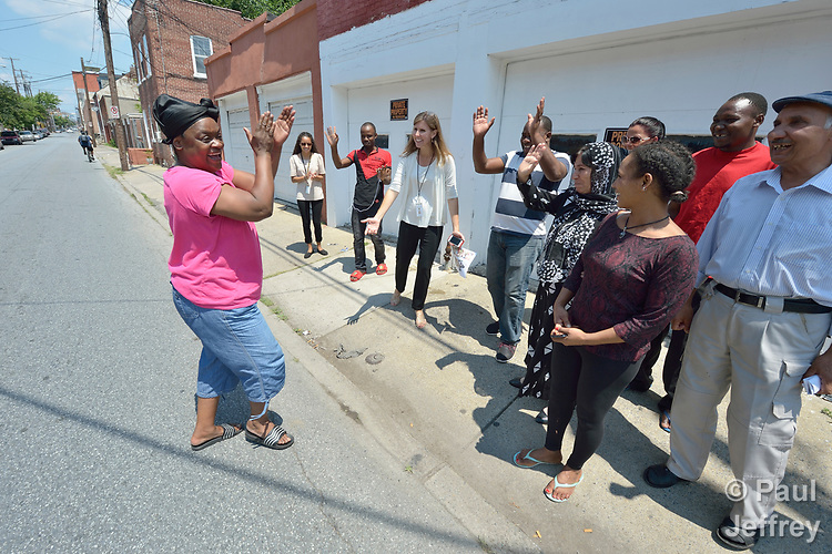 As members of a cultural orientation class for newly arrived refugees walked together on a street in downtown Lancaster, Pennsylvania, the woman on the left came out of her home and crossed the street, clapping her hands and repeating, &quot;Welcome to America!&quot; <br /> <br /> The class was sponsored by Church World Service. <br /> <br /> Photo by Paul Jeffrey for Church World Service.
