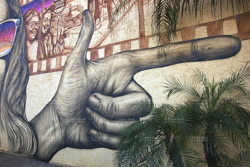 USA. Arizona state. Phoenix. A graffiti on an art school's wall of a hand with two fingers pointed like when a man shoots a gun. A firearm is a portable gun, being a barreled weapon that launches one or more projectiles often driven by the action of an explosive force. Most modern firearms have rifled barrels to impart spin to the projectile for improved flight stability. The word firearms usually is used in a sense restricted to small arms (weapons that can be carried by a single person). The right to keep and bear arms is a fundamental right protected in the United States by the Second Amendment of the Bill of Rights in the Constitution of the United States of America and in the state constitutions of Arizona and 43 other states. 27.01.16 © 2016 Didier Ruef