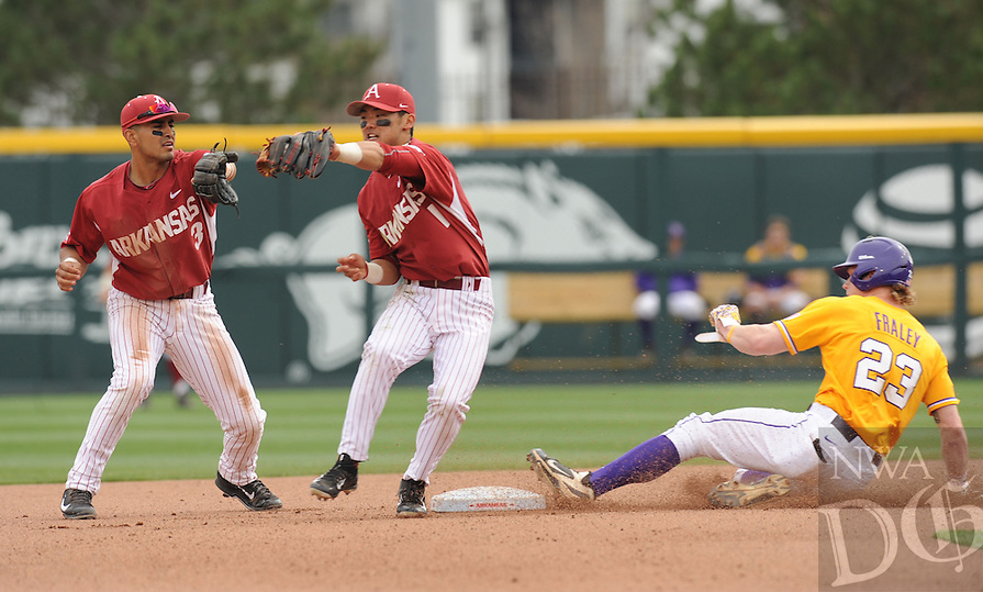 NWA Democrat-Gazette/ANDY SHUPE - Second baseman Rick Nomura (center) of Arkansas fields the late throw from the plate as shortstop Michael Bernal (right) backs up the play while Jake Fraley of LSU comes in safely at the bag during the seventh inning Saturday, March 21, 2015, at Baum Stadium in Fayetteville. Visit nwadg.com/photos for more photos from the game.