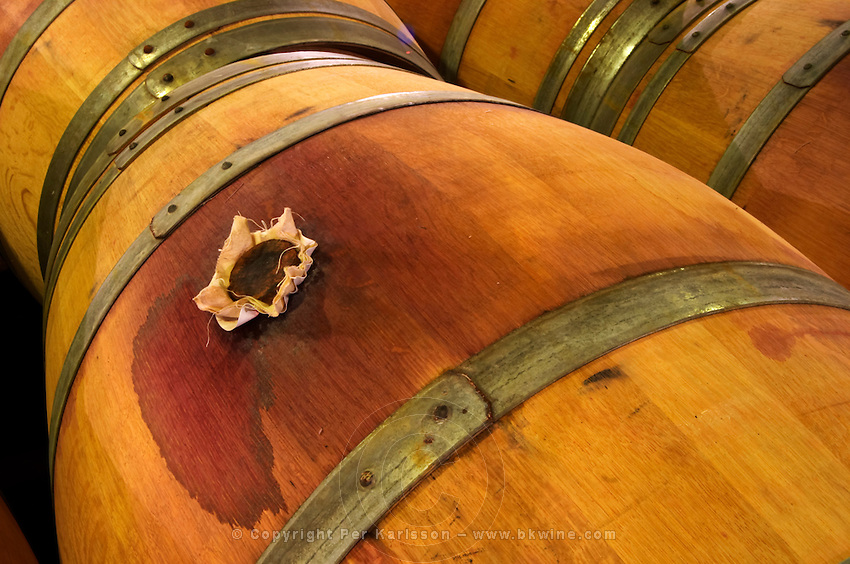 An oak barrel stained by wine with a bung hole stopper in wood covered in jute to make it tight  Chateau de Haux Premieres Cotes de Bordeaux  Entre-deux-Mers  Bordeaux Gironde Aquitaine France