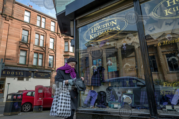 Ann elderly woman passes the premises of kilt maker Houston, which has the Paisley museum reflected in its window.