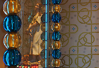Statue reflected in the glass of the cabinet of censers with its gold and blue glass beads by Murano glassmaker Salviati, in the Bell tower room themed 'Le Merveilleux' or The Supernatural, first floor, in Le Tresor de la Cathedral d'Angouleme, in Angouleme Cathedral, or the Cathedrale Saint-Pierre d'Angouleme, Angouleme, Charente, France. The 12th century Romanesque cathedral was largely reworked by Paul Abadie in 1852-75. In 2008, Jean-Michel Othoniel was commissioned by DRAC Aquitaine - Limousin - Poitou-Charentes to display the Treasure of the Cathedral in some of its rooms, which opened to the public on 30th September 2016. The hand printed wallpaper by Atelier d'Offard uses interlacing patterns reminiscent of the Neo-Romanesque period of the 19th century. Picture by Manuel Cohen. L'autorisation de reproduire cette oeuvre doit etre demandee aupres de l'ADAGP/Permission to reproduce this work of art must be obtained from DACS.