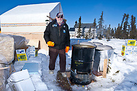 Volunteer Jim Paulis stands proudly next to his invention that has been called *The biggest dog cooker on earth* at Cripple during the 2010 Iditarod