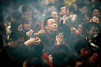 A man prays while holding high his incense sticks at the Jade Buddha Temple in Shanghai, China. The first day of the Chinese New Year is one of the most auspicious days in the year to offer incense and prayers..18 Feb 2007