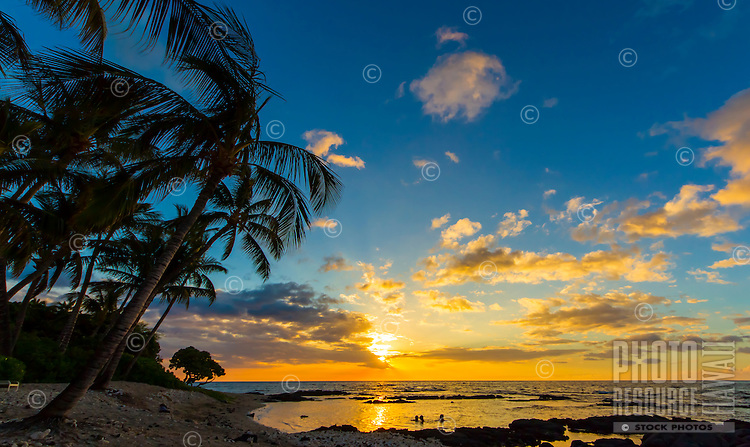 At sunset, a family cools off on a warm summer night in a tide pool in Puako, Big Island.