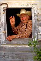a portrait of a very real and very old cowboy as he poses in the window of his horse stable. Howard. Texas United States a window in rural stable on a ranch.