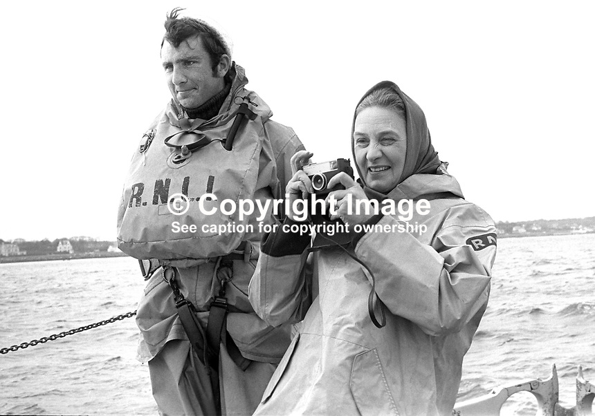 Mrs Celia Whitelaw, wife of William Whitelaw, secretary of state for N Ireland, with her camera taking photographs aboard the Sir Samuel Kelly during a visit to the Donaghadee Lifeboat Station, Co Down, 28th March 1973.  Also in the photo is crewman Quinton Nelson. 197303280158d<br /> <br /> Copyright Image from Victor Patterson, 54 Dorchester Park, Belfast, UK, BT9 6RJ<br /> <br /> t1: +44 28 9066 1296 (from Rep of Ireland 048 9066 1296)<br /> t2: +44 28 9002 2446 (from Rep of Ireland 048 9002 2446)<br /> m: +44 7802 353836<br /> <br /> e1: victorpatterson@me.com<br /> e2: victorpatterson@gmail.com<br /> <br /> The use of my copyright images is subject to my Terms &amp; Conditions.<br /> <br /> It is IMPORTANT that you familiarise yourself with them. They are available on my website at www.victorpatterson.com.<br /> <br /> None of my copyright images may be used on a website unless they are visibly watermarked, i.e. &copy; Victor Patterson within the body of the visible image. Metadata denoting my copyright must NOT be deleted. <br /> <br /> Web use (maximum size - 300 kb) is extra at currently recommended NUJ rates.