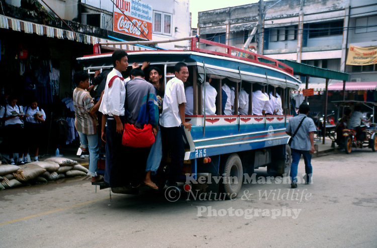 A songthaew loaded with young students on the way home from school. Chiang Mai - Northern Thailand.