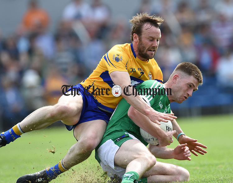 John Hayes of Clare in action against Seamus O Carroll of Limerick during their Munster championship quarter-final game in Cusack park. Photograph by John Kelly.
