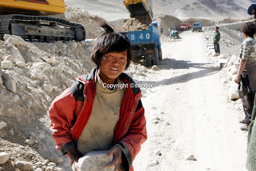 "A young boy carries rocks to build the road to Mt Everest.<br /> China started building a controversial 67-mile ""paved highway fenced with undulating guardrails"" to Mount Qomolangma, known in the west as Mount Everest, to help facilitate next year's Olympic Games torch relay.<br /> Tibet, China<br /> July, 2007"