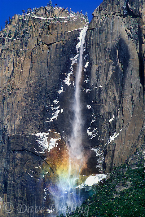 799451297 a rainbow forms at the base of upper yosemite falls framed by patches of snow seen from the valley floor in yosemite national park california