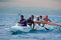 Young Tahitian men paddling six man canoe in lagoon while training for a race, with a sailboat in the background