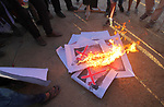 Palestinian protesters burn posters depicting US President Donald Trump during clashes with Israeli troops in tents protest where Palestinians demand the right to return to their homeland at the Israel-Gaza border, in east of Gaza city on September 7, 2018. Photo by Dawoud Abo Alkas