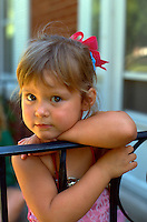 Child age 3 leaning on railing fence with curious look on face.  Western Springs  Illinois USA