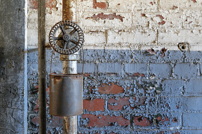 Old pipe and valve with rusty hanging bucket, peeling and flaking paint for an industrial grunge background with copy space.