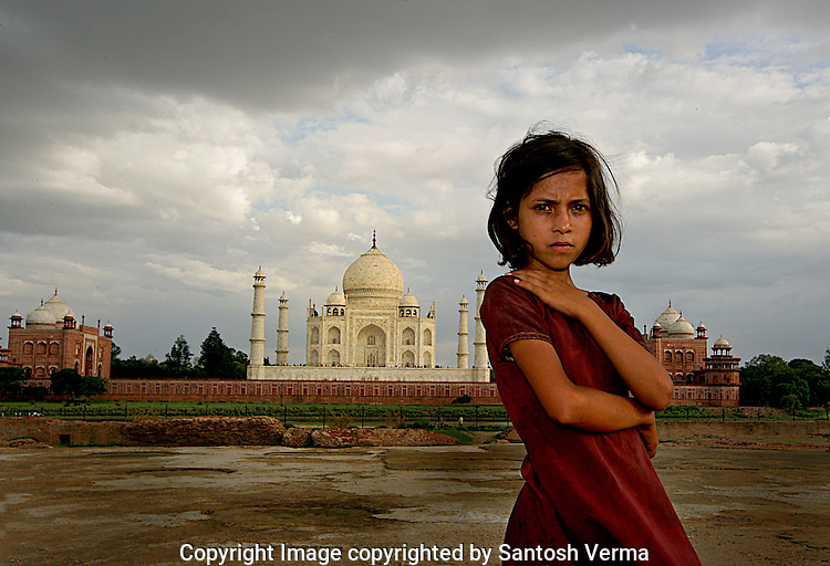 A young girl child who lives in the villages behind the world's most famous historical monument The Taj Mahal, watches intently and with certainty that the mounument behind her is the focus of attention and importance for the photographer. Photograph © Santosh Verma
