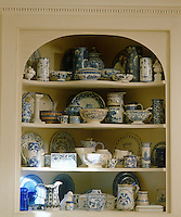 A detail of some open shelves in a living room displaying a large and eclectic collection of blue-and-white porcelain