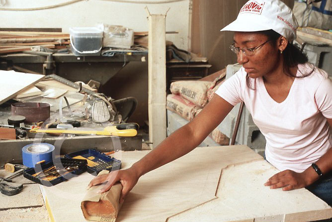 Young woman interning in conservation exhibits department of municipal museum sanding in workshop
