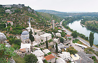 View from the hilltop tower over the town with mosque and church, rooftops. Neretva river. Pocitelj historic Muslim and Christian village near Mostar. Federation Bosne i Hercegovine. Bosnia Herzegovina, Europe.