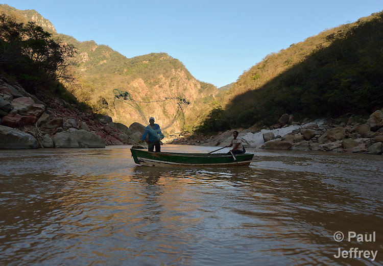 Tomas Rivero rows the boat as Samuel Delgado casts a net as the two men fish on the Pilcomayo River outside of Villamontes, Bolivia. Rivero is a leader of the Union of Pilcomayo River Fishers, and an advocate for cleaning up the river, which has been plagued by contamination from upstream mining and road construction. This portion of the river is inside the protected Aguaragüe National Park and Integrated Management Natural Area.