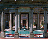 A circular colonnade at the Tettuccio spa surrounds a pool bordered with red geraniums