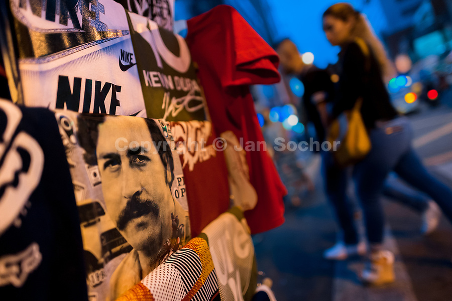 """A t-shirt for sale, depicting the drug lord Pablo Escobar, is seen arranged at the market stand on the street in Medellín, Colombia, 2 December 2017. Twenty five years after Pablo Escobar's death, the legacy of the Medellín Cartel leader is alive and flourishing. Although many Colombians who lived through the decades of drug wars, assassinations, kidnappings, reject Pablo Escobar's cult and his celebrity status, there is a significant number of Colombians who admire him, worshipping the questionable """"Robin Hood"""" image he had. Moreover, in the recent years, the popular """"Narcos"""" TV series has inspired thousands of tourists to visit Medellín, creating a booming business for many but causing a controversial rise of narco-tourism."""