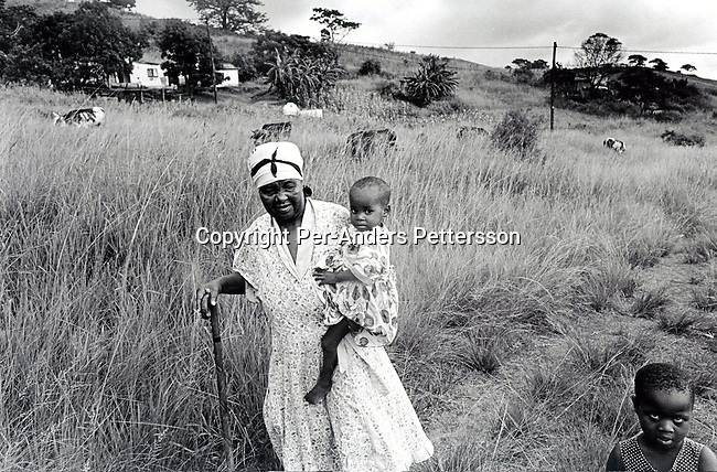 MURCHISON, SOUTH AFRICA - FEBRUARY 26: An unidentified grandmother carries her daughter's child outside their home on February 26, 2002 in Murchison, a rural area in Natal, South Africa. The mother died recently from an Aids related disease, and the grandmother is taking care of the child. A hospice called South Coast Hospice visits patients in their homes in the area and gives them counseling and emotional support. South Africa has the highest infection rate in the world with about 4.5 million people infected by HIV-Aids and is fighting hard to educate the population on safe sex practices and the importance of abstinence for young people..Photo: Per-Anders Pettersson/ iAfrika Photos.
