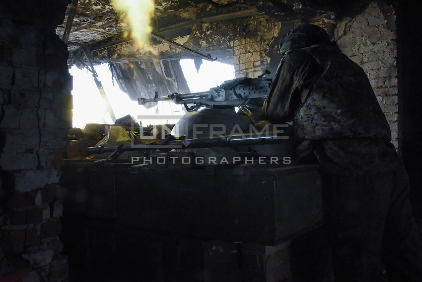 A Russia-backed rebel fires at Ukrainian army positions at Donetsk airport, eastern Ukraine, Friday, June 12, 2015.