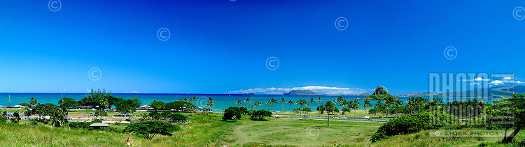 Panorama of peaceful green Kualoa Beach Park on Windward Oahu with Chinaman's Hat surrounded by turquoise water in the distance.