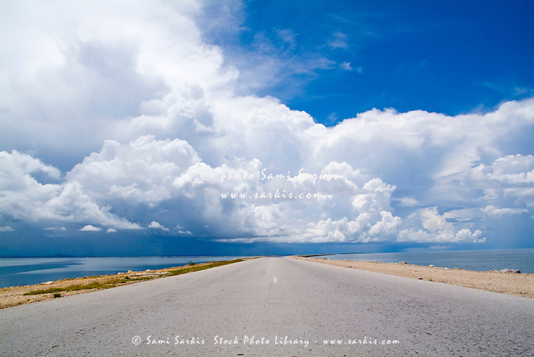 Deserted rural road on the way to Cayo Santa-Maria with the sea on either side, Cuba.