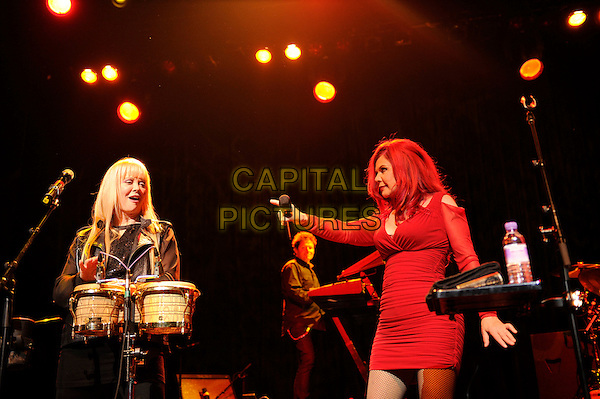 Cindy Wilson and Katie Pierson<br /> The B 52's performing in concert, Indigo2, Greenwich, London, England. 16th August 2013<br /> on stage in concert live gig performance performing music half length black leather jacket drums red dress side profile hand arm pointing <br /> CAP/MAR<br /> &copy; Martin Harris/Capital Pictures