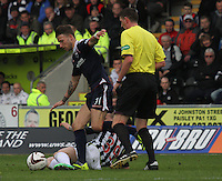 Gregg Wylde tackles Melvin De Leeuw watched by Referee Craig Thomson in the St Mirren v Ross County Scottish Professional Football League Premiership match played at St Mirren Park, Paisley on 3.5.14.