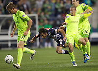 CF Monterrey forward is pushed to the ground by  Seattle Sounders FC defender Zach Scott, right, w while teammates Jeff Parke, left, and Osvaldo Alonso defend during a CONCACAF Champions League match between the Seattle Sounders FC and CF Monterrey at CenturyLink Field in Seattle Tuesday Oct. 18, 2011. CF Monterrey won the game 2-1.