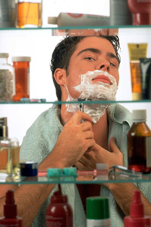 Handsome young man shaves in the bathroom, as seen through a medicine cabinet. man shaving. United States.