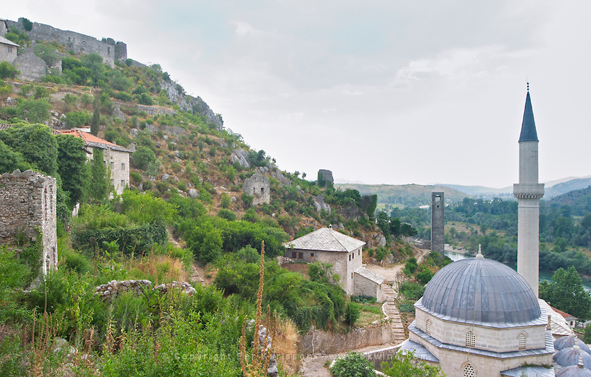 View over the town with mosque and church towers. River Neretva.. House ruins on the hillside. Pocitelj historic Muslim and Christian village near Mostar. Federation Bosne i Hercegovine. Bosnia Herzegovina, Europe.