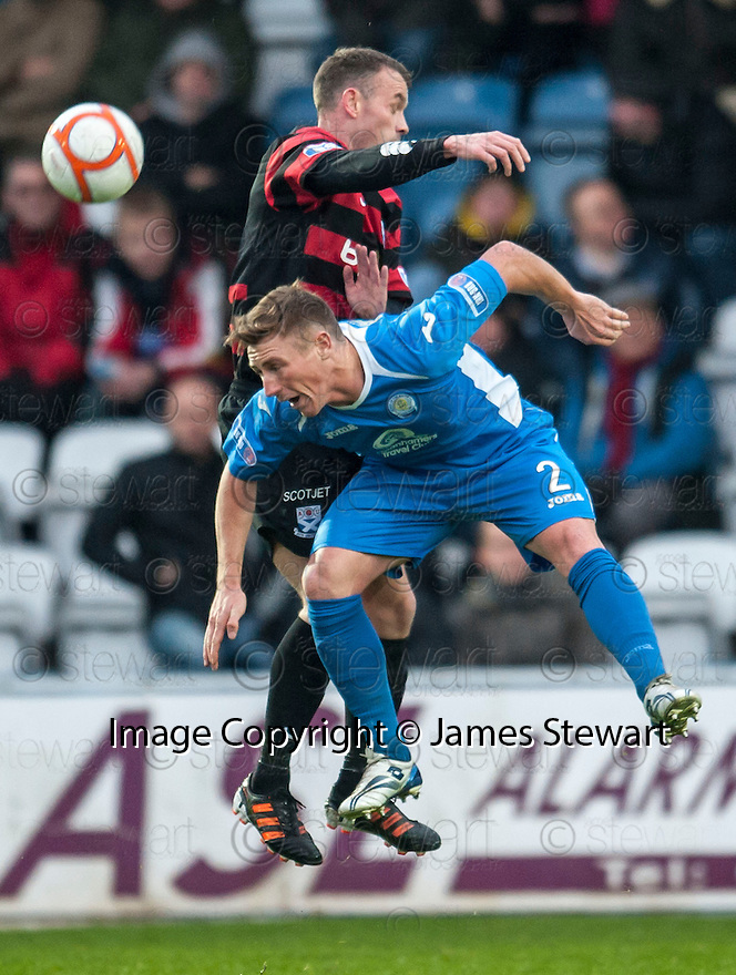 Queen of the South's Chris Mitchell and Ayr Utd's Player / Manager Mark Roberts challenge for the ball.