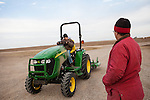 Aidan Baalman, left, 10, drives a tractor under the supervision of his aunt, Keyna Baalman, on the family's 12,000-acre farm outside of Hoxie, Kan. on Friday, Oct. 12, 2012. As historically dry conditions continue, farmers from South Dakota to the Texas panhandle rely on the Ogallala Aquifer, the largest underground aquifer in the United States, to irrigate crops. After decades of use, the falling water level ? accelerated by historic drought conditions over the last two years ? is putting pressure on farmers to ease usage or risk becoming the last generation to grow crops on the land. Farmers like Mitchell Baalman and Brett Oelke (both not pictured) are part of a farming community in in Sheridan County, Kansas, an agricultural hub in western Kansas, who have agreed to cut back on water use for crop irrigation so that their children and future generations can continue to farm and sustain themselves on the High Plains.