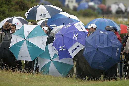 17 July 2008: Crowds shelter from the rain during the first round of the Open Championship at Royal Birkdale Photo: Neil Tingle/Action Plus..080717 golf spectator fan wet weather umbrella