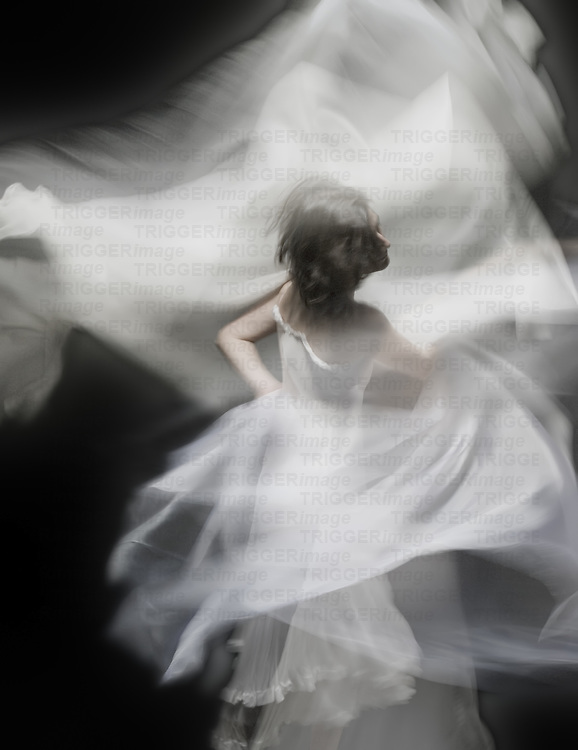A young woman dancing with a white dress