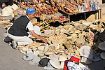 A man arranges the baskets and hats he is selling in the Souk in Marrakesh, Morocco.