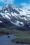 Alaska, Kenai Fjords National Park, hiker ascends stream toward Kenai Mountains,..