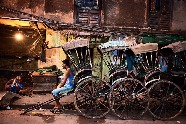 "RICKSHAWS, KOLKATA               April 4, 2010                                         As of 2005, the last sizeable fleet of rickshaws can be found in Kolkata , where the rickshaw puller union resisted prohibition. Several major streets have been closed to rickshaw traffic since 1972, and in 1982 the city seized over 12,000 rickshaws and destroyed them. In 1992, it was estimated that over 30,000 rickshaws were operating in the city, all but 6,000 of them illegally, lacking a license (no new licenses have been issued since 1945). The large majority of rickshaw pullers rent their rickshaws for a few dollars per shift.  Some pullers sleep in the streets in their rickshaws. In August 2005, the Communist government of West Bengal announced plans to completely ban rickshaws, resulting in protests and strikes of the pullers. .In 2006, the Chief Minister of West Bengal, Buddhadeb Bhattacharya, announced that rickshaws would be banned and that rickshaw pullers would be rehabilitated.Kolkata rickshaws serve people ""just a notch above poor"" who tend to travel short distances. He added that some people use rickshaws as ""24 hour ambulance services,"" as escorts for shoppers, and as a way for businesses to transport goods.  Many middle class families contract with rickshaw pullers to transport their children; a rickshaw puller who transports children becomes a ""family retainer.Some Kolkatans do not like to ride in rickshaws because they feel offended by the idea of a human pulling them, and that some of them question the government's motives on banning rickshaws. Rudrangshu Mukerjee, an academic  said that he does not want to be carried in a rickshaw but does not like the idea of ""taking away their livelihood.When Kolkata floods rickshaw business increases and prices rise. Pic Graham Crouch"