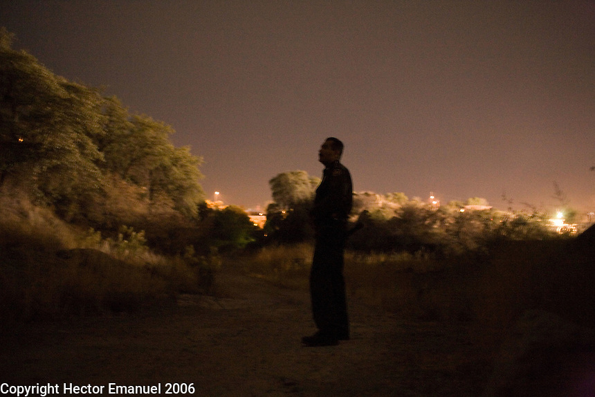 Border Patrol agent Luis Chavez waits in the dark for a group of people that have been spotted crossing the border..Nogales, AZ.12/10/05.photos: Hector Emanuel