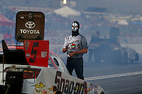 Oct 31, 2014; Las Vegas, NV, USA; A crew member wears a Halloween mask as he backs up NHRA funny car driver Cruz Pedregon during qualifying for the Toyota Nationals at The Strip at Las Vegas Motor Speedway. Mandatory Credit: Mark J. Rebilas-USA TODAY Sports