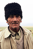 Romania, Central Europe. An older unshaven shepherd with blue eyes and a traditional black lambswool hat.