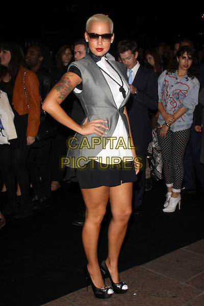 AMBER ROSE .The Ozwald Boateng Fashion Show during the final day of London Fashion Week, Odeon cinema Leicester Square London, England, UK..September 22nd 2010.full length black white dress hand on hip sunglasses shades shirt sleeveless jacket waistcoat collar skirt silver shoes africa pendant necklace tattoo grey gray.CAP/AH.©Adam Houghton/Capital Pictures.