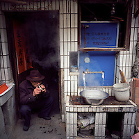 An elderly man drinks tea at a communal hot water station in the old city area of Yangzhou, Jiangsu province, 2012. (Mamiya 6, 50mm, Kodak Ektar 100 film)