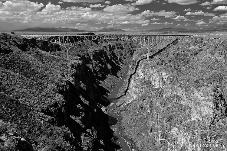 The steel deck arch Rio Grande Gorge Bridge carries U.S. Route 64 traffic across Rio Grande Gorge 10 miles northwest of Taos, New Mexico. Dedicated in September of 1964 the Rio Grande Gorge Bridge is the seventh highest bridge in the United States.