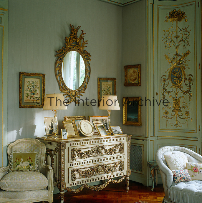 In the Duchess of Windsor's bedroom a large mirror and some small paintings in gilt frames hang above an elaborate carved chest of drawers