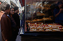 Paris, France. 09.05.2015. Customers look at pastries in a patisserie, Rue Mouffetarde, 5th Arrondissement, Paris, France. Photograph © Jane Hobson.